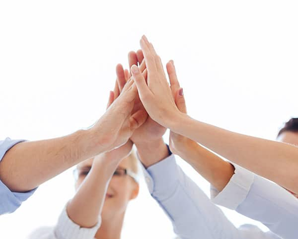 Five men and woman put their hands together in a high five unison as Gallagher Hospice celebrates Volunteer Appreciation Week!